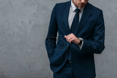 Photo for Cropped shot of businessman in stylish suit looking at watch in front of concrete wall - Royalty Free Image