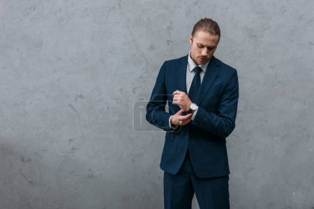 young serious businessman in stylish suit buttoning cuffs
