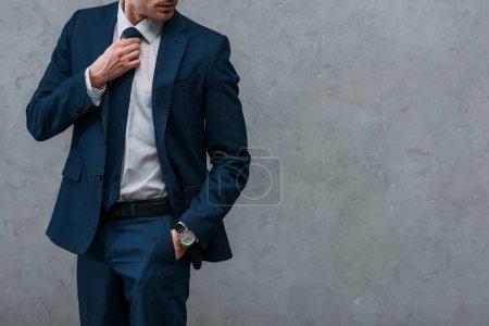 Photo pour Recadrée tir de bel homme d'affaires en costume élégant en face de mur en béton - image libre de droit