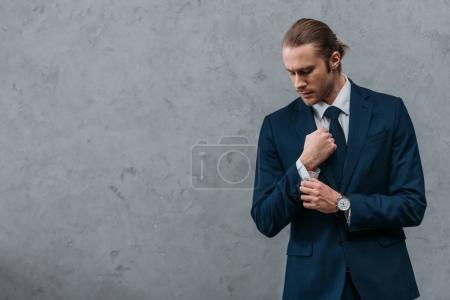 young handsome businessman in stylish suit buttoning cuffs