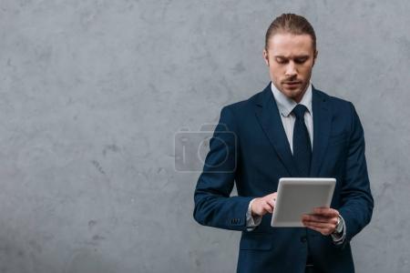 Foto de Joven empresario serio uso tableta frente a muro de hormigón - Imagen libre de derechos