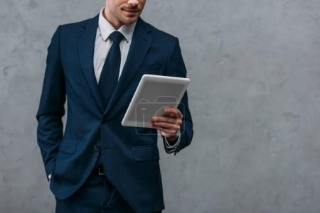 Photo for Cropped shot of businessman using tablet in front of concrete wall - Royalty Free Image