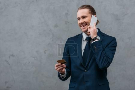 young smiling businessman with credit card and phone making e-shopping