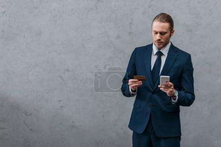 young handsome businessman with credit card and smartphone making e-shopping