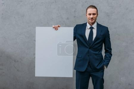 young smiling businessman holding blank board in front of concrete wall