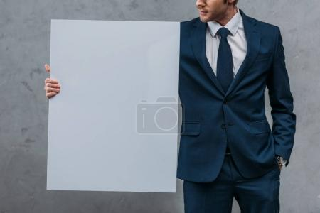 cropped shot of handsome businessman holding blank board in front of concrete wall