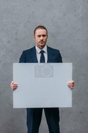 Photo pour Jeune entrepreneur confiant tenant Conseil vide devant le mur de béton - image libre de droit