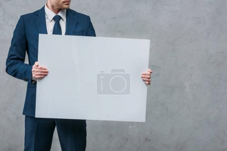 cropped shot of businessman holding blank board in front of concrete wall