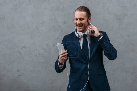 young happy businessman with headphones and smartphone