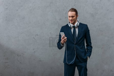 young handsome businessman with headphones and smartphone