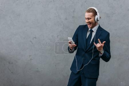 young businessman listening music with headphones and smartphone and making rock gesture