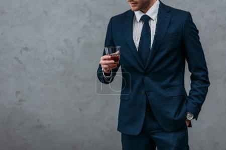 cropped shot of handsome businessman with glass of whiskey