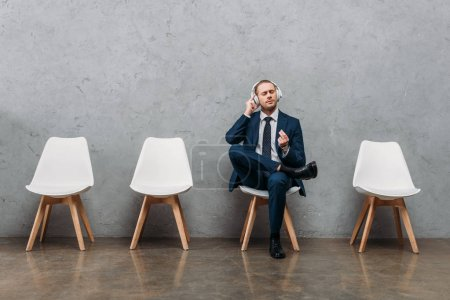 young handsome businessman listening music with headphones while sitting on chair