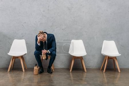 Photo for Lonely businessman drinking alcohol while sitting on chair under concrete wall - Royalty Free Image