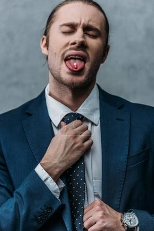 addicted businessman sticking out tongue with drug pill