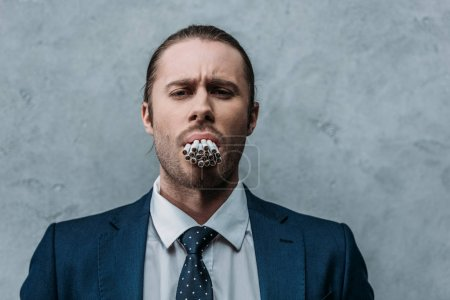 cropped shot of businessman with mouth full of cigarettes