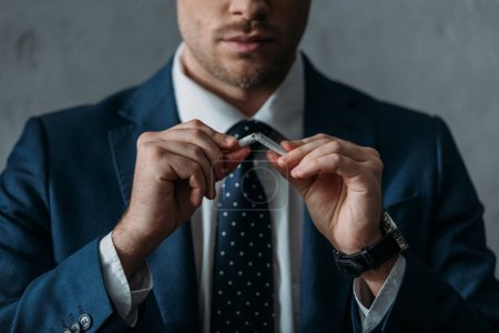 cropped shot of businessman breaking cigarette