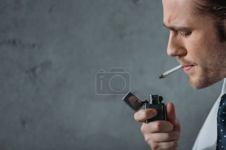 close-up portrait of man smoking cigarette in front of concrete wall