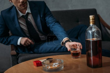 Photo for Cropped shot of businessman taking glass of whiskey from table - Royalty Free Image