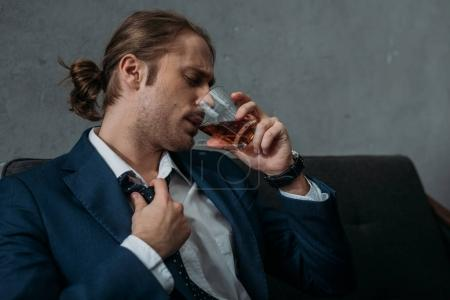 young alcohol addicted businessman drinking whiskey