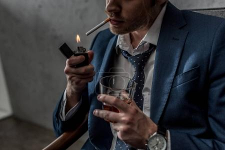 Photo for Cropped shot of businessman with glass of whiskey smoking cigarette - Royalty Free Image