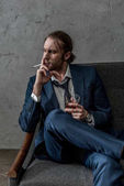 young alcohol addicted businessman with glass of whiskey smoking cigarette