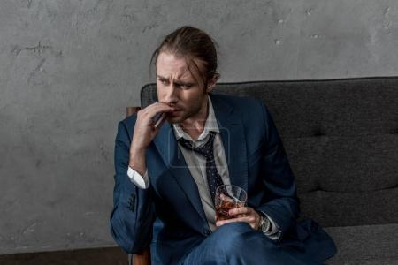 drunk alcohol addicted businessman with glass of whiskey smoking cigarette