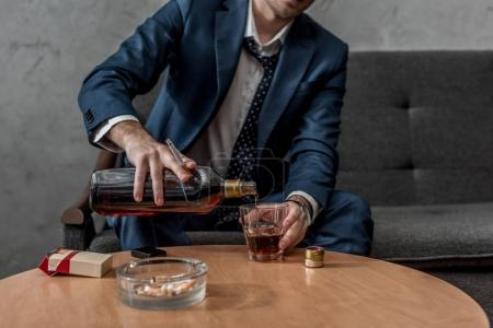 Photo for Cropped shot of alcohol addicted businessman drinking whiskey while sitting on couch - Royalty Free Image