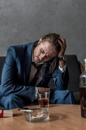 Photo for Drunk depressed businessman sitting on couch with glass of whiskey on table - Royalty Free Image