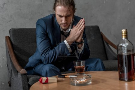 Photo for Depressed thoughtful businessman with glass and bottle of whiskey sitting on couch - Royalty Free Image