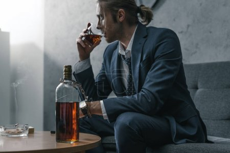 Photo for Alcohol addicted businessman with glass and bottle of whiskey sitting on couch - Royalty Free Image