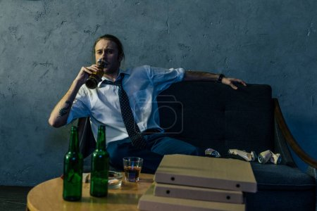 Photo for Drunk alcohol addicted man drinking beer with pizza on couch after work - Royalty Free Image