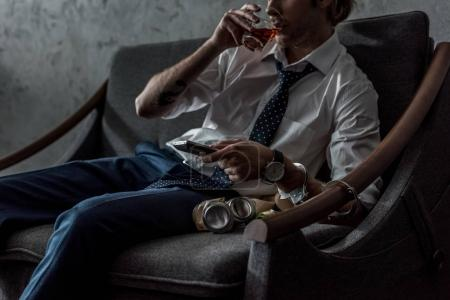Photo for Cropped shot of alcohol addicted man in white shirt watching tv and drinking whiskey after work - Royalty Free Image