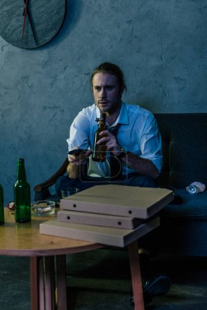 young alcohol addicted man in white shirt watching tv and drinking beer after work on couch