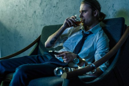alcohol addicted man in white shirt watching tv and drinking whiskey after work