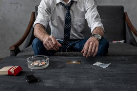 cropped shot of businessman with drug addiction preparing to take cocaine