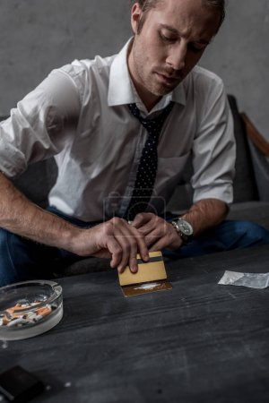 Photo for Businessman with drug addiction preparing to take cocaine - Royalty Free Image