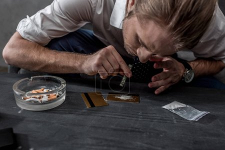 close-up shot of businessman with drug addiction sniffing cocaine