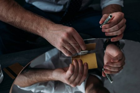 cropped shot of businessman with drug addiction sniffing cocaine from mirror