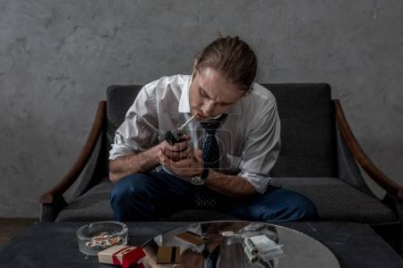 businessman with drug addiction smoking cigarette above table with various drugs