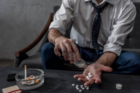 businessman with drug addiction pouring pills on hand from bottle