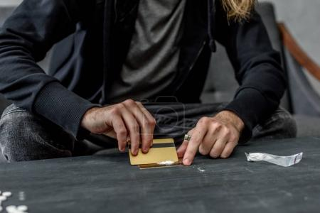 cropped shot of addicted man preparing to take cocaine