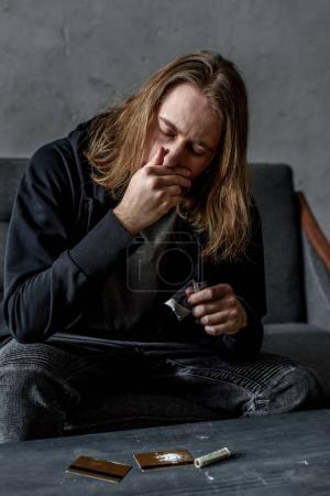 Photo for Addicted man sniffing cocaine while sitting on couch - Royalty Free Image