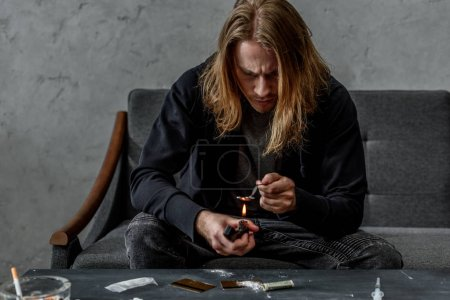 addicted junkie boiling heroin in spoon with lighter while sitting on couch