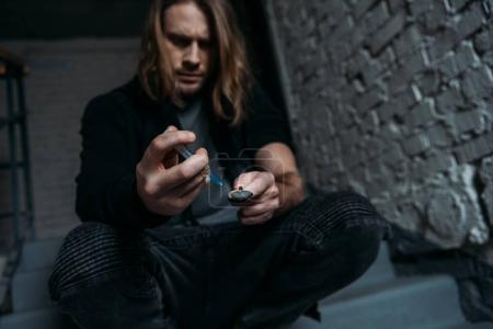 Photo for Addicted junkie filling syringe with heroin from spoon - Royalty Free Image