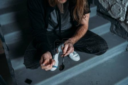 cropped shot of addicted junkie filling syringe with heroin from spoon