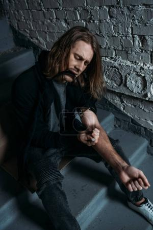addicted junkie doing heroin injection on stairs