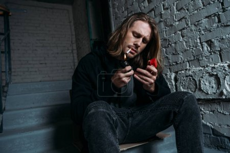 young man smoking cigarette while sitting on stairs