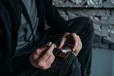cropped shot of addicted junkie sniffing cocaine from credit card