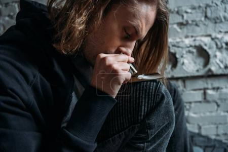 close-up portrait of addicted man sniffing cocaine from credit card
